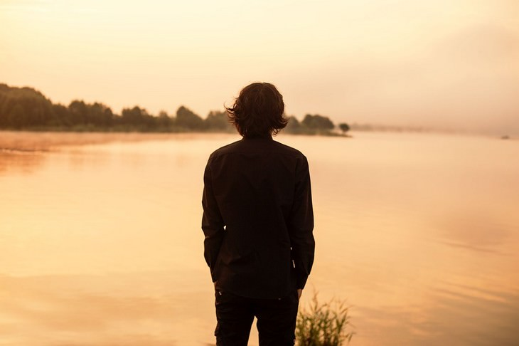 דברים בחיים שלא ניתן לשנות: גבר עומד מול אגם בשעת שקיעה