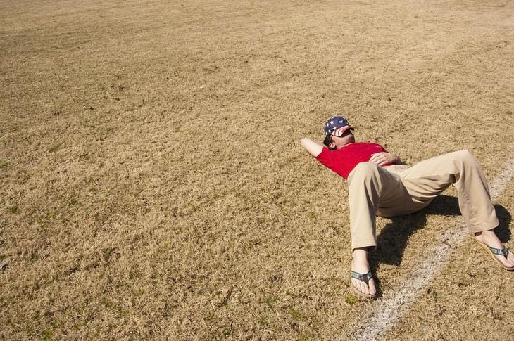 הקשר בין בעיות שינה ואלצהיימר: גבר עם כובע על פניו ישן בשדה