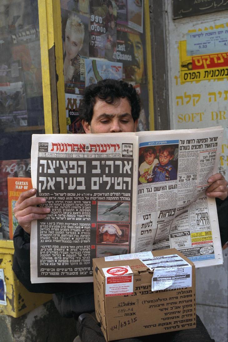 מלחמת המפרץ: מבט מודאג של אזרח עם עיתון ביד וערכת מגן שנפתחה