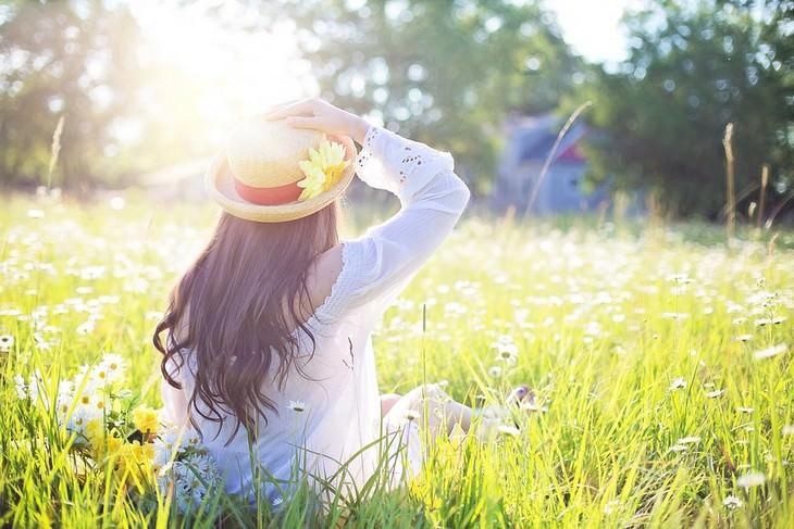איך להחזיר את השליטה לחייכם: אישה יושבת בשדה ואוחזת בכובעה
