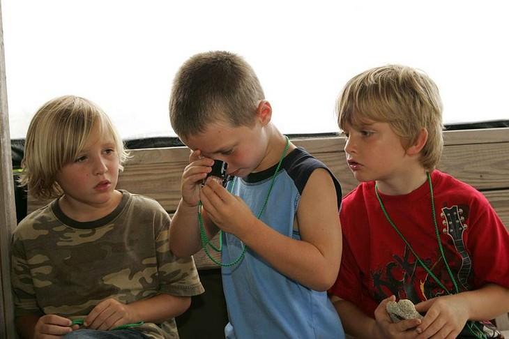 בדיחה גסה: שלושה בנים שאחד מהם מביט דרך עדשת פלסטיק