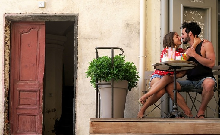 הרגלים של זוגות עם חיי מין מוצלחים: גבר ואישה יושבים בבית קפה חבוקים עם מבט מלא תשוקה