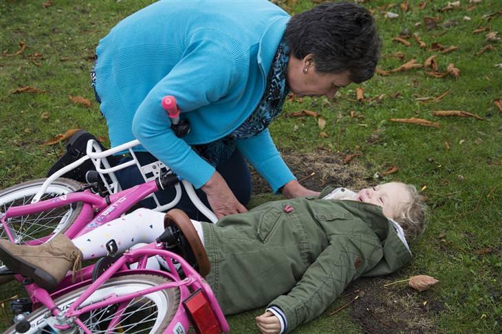 זכויות של הורים ותלמידים: אישה מבוגרת מרימה ילדה שנפלה מאופניים