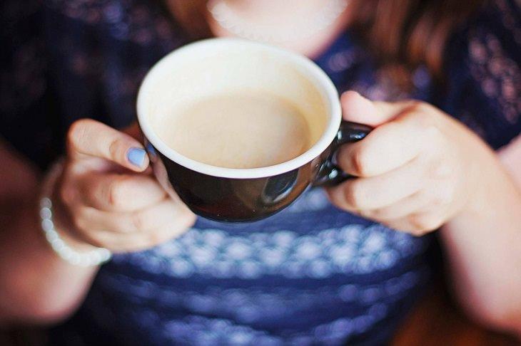 דברים שאסור לעשות על בטן ריקה: אישה אוחזת בספל קפה