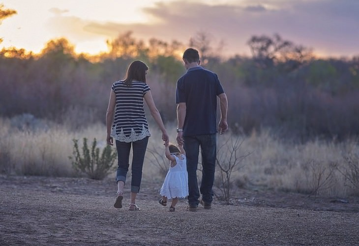 הרגלים גרועים של הורים שצריך לשבור: הורים הולכים יד ביד עם ילדתם בשדה