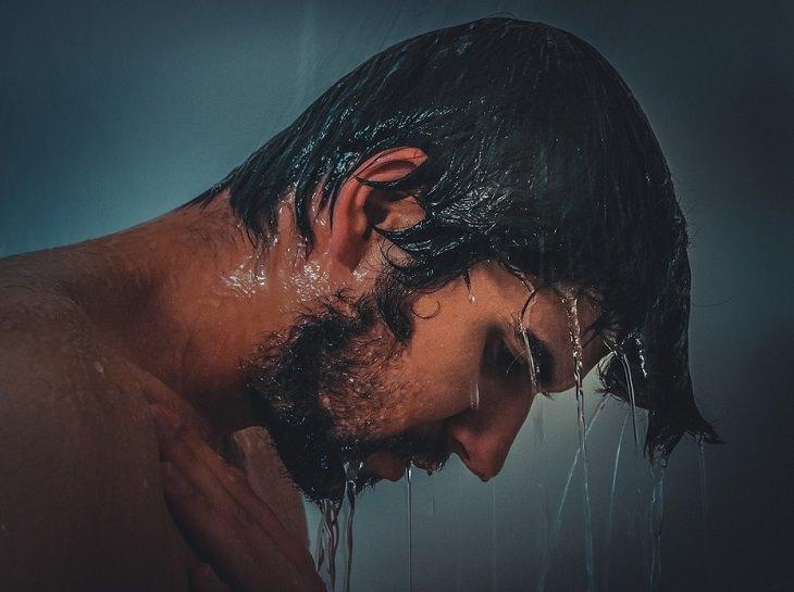 סיבות וטיפולים לגירוד בראש: גבר שוטף את שיערו במקלחת