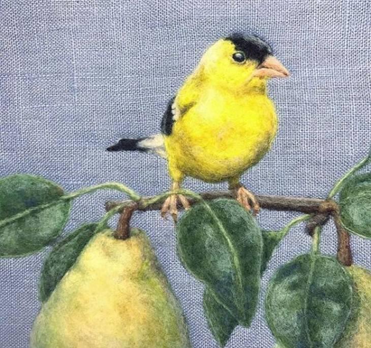 רקמות לבד של חיות: ציפור עומדת על ענפים של עץ אגסים