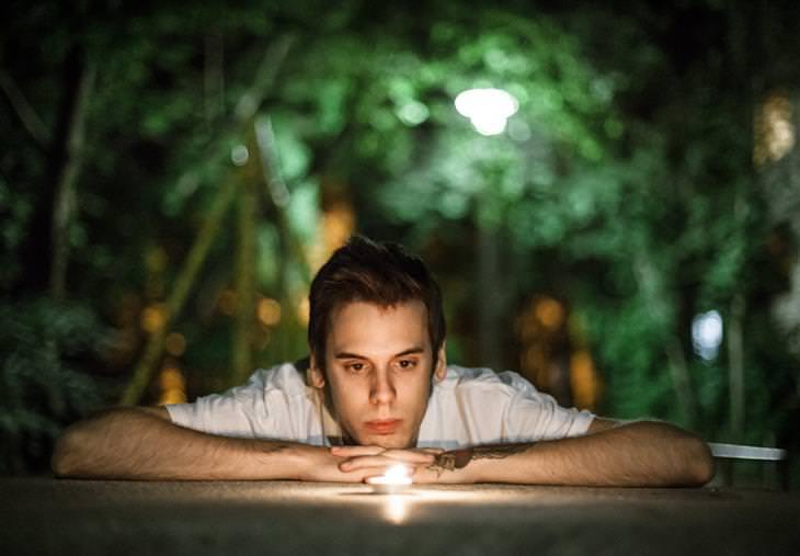 טיפים להתמודדות עם התקפי חרדה: איש רוכן על שולחן ומביט בנר קטן
