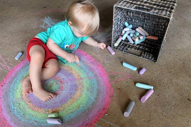 איך לגדל ילדים שיודעים לחשוב בצורה יצירתית: ילד מצייר עיגולים צבעוניים עם גירים על הרצפה