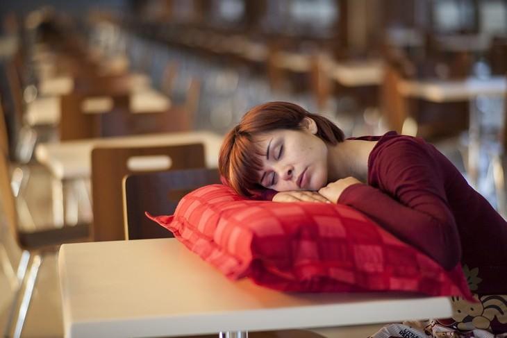 סיבות לעלייה במשקל: אישה ישנה על כרית שמונחת על שולחן