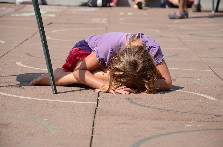 שקרים שהורים מספרים לילדים: ילדה שוכבת עם הפנים כלפי האדמה על מגרש משחקים