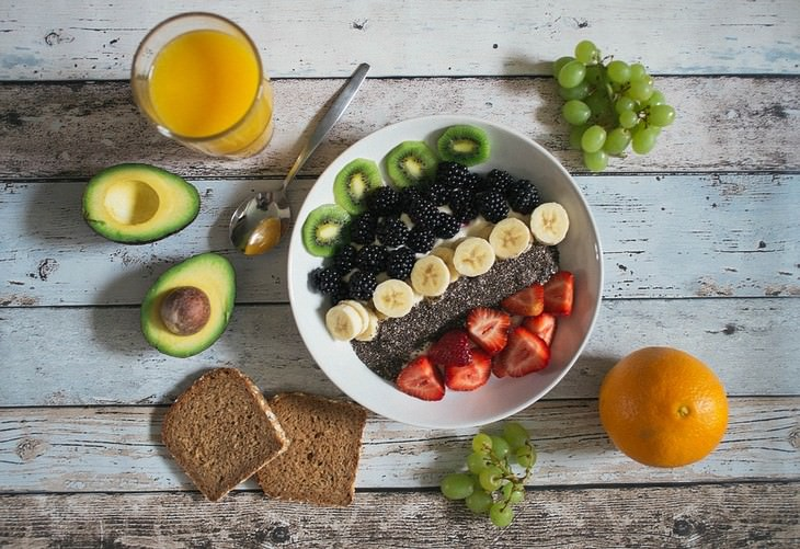 סיבות לעלייה במשקל: קערה עם פירות מוקפת פירות, לחם ואבוקדו