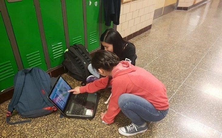 """שיטות חינוך בארה""""ב: שתי תלמידות עם לפטופ במסדרון בית ספר"""
