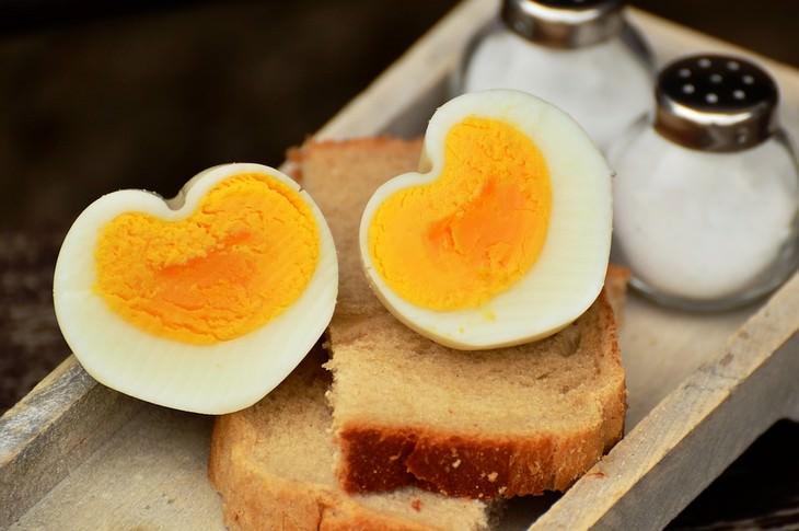 סיבות לעלייה במשקל: ביצה חצויה בצורת לב מונחת על פרוסת לחם לצד מלחיות