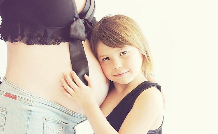 מידע על בדיקת מי שפיר - ילדה נשענת על בטן של אישה בהריון