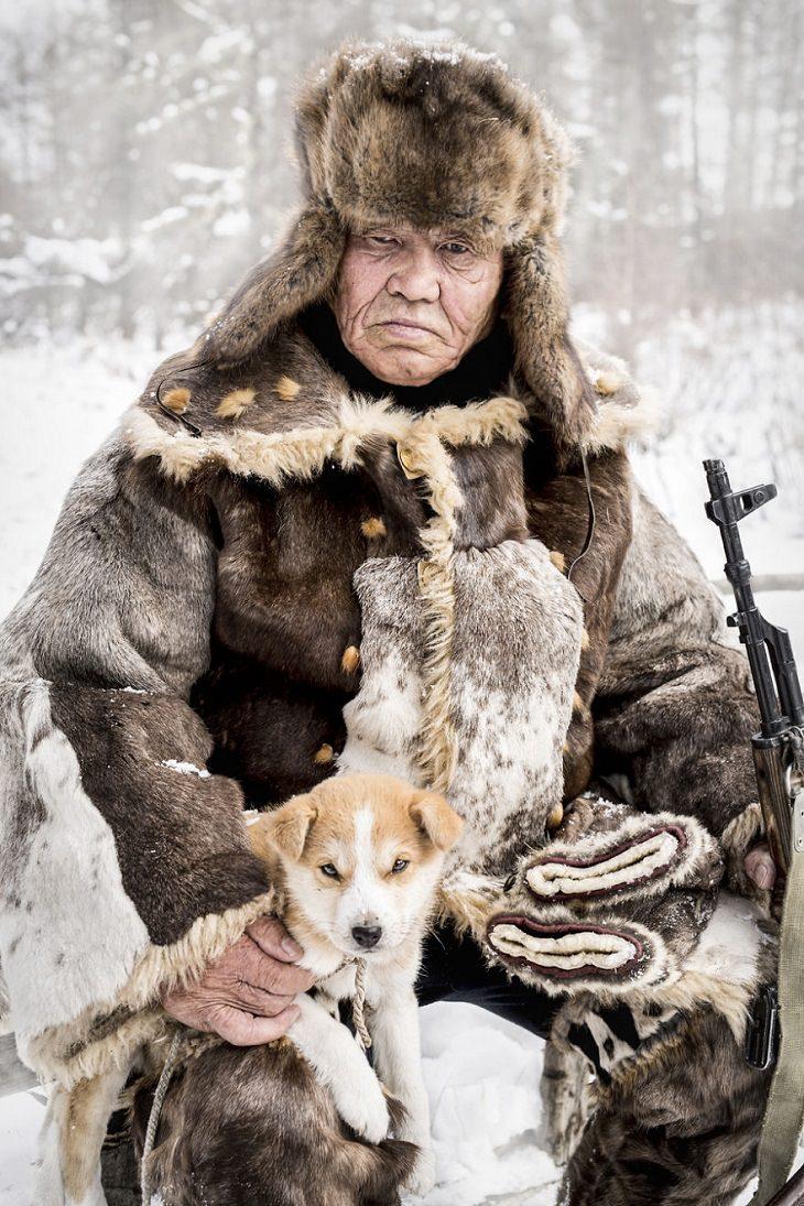 תרבויות מיוחדות בסיביר: אדם אוונקי מבוגר יושב בשלג כשכלבו בחיקו
