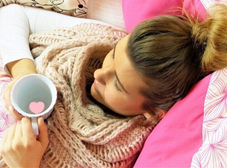 מקומות עבודה מפנקים: אישה שוכבת על מיטה עם כוס משקה חם בידה שבתוכה לב
