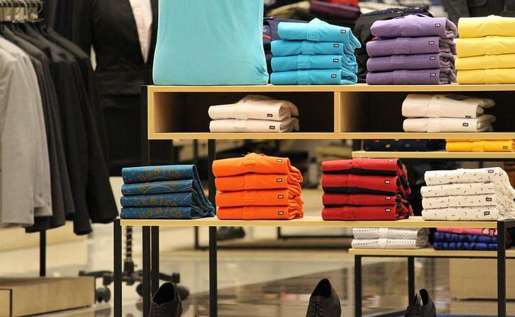 מדריך רכישת בגדים ובדים איכותיים: תצוגת חולצות מקופלות בחנות בגדים