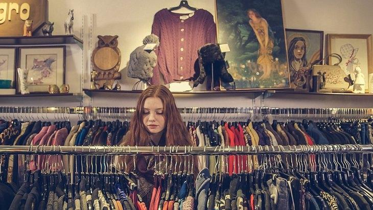 מדריך רכישת בגדים ובדים איכותיים: נערה בוחנת מתלה עם בגדים בחנות