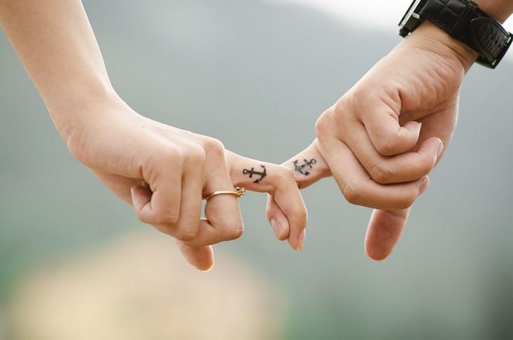 איך לפתור ריבים? זוג מחזיק אצבעות עם ציורי עוגנים