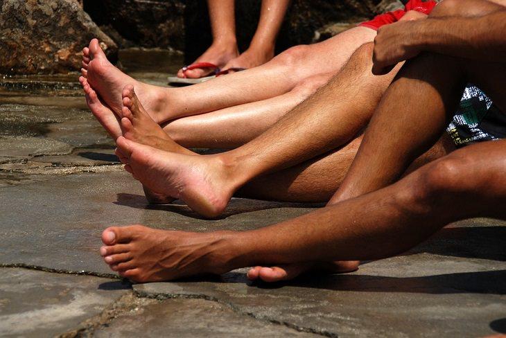 סיבות וטיפולים לריח רע ברגליים: רגליים חשופות על מדרכה רטובה