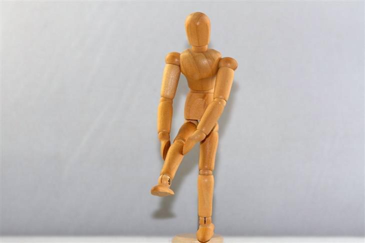 אנשים שבקבוצת סיכון לסבול מחוסר ויטמין D: בובת עץ בתנוחה שבה היא מחזיקה את הברך שלה בידיה