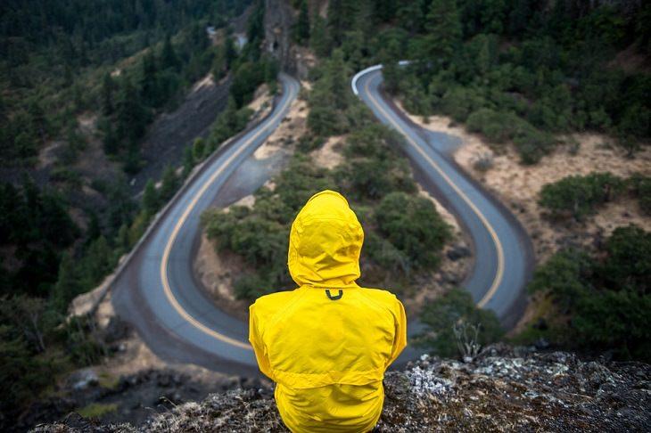סימנים שאתם בדרך הנכונה: גבר יושב על הר הצופה לכביש מפותל