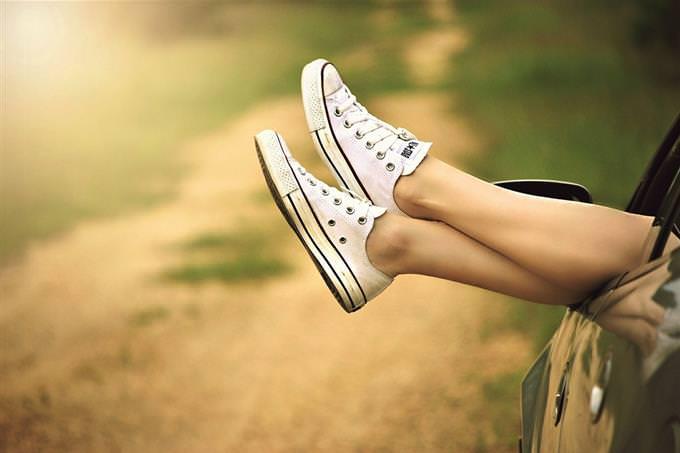 רגליים של אישה נתלות מחוץ לחלון של רכב