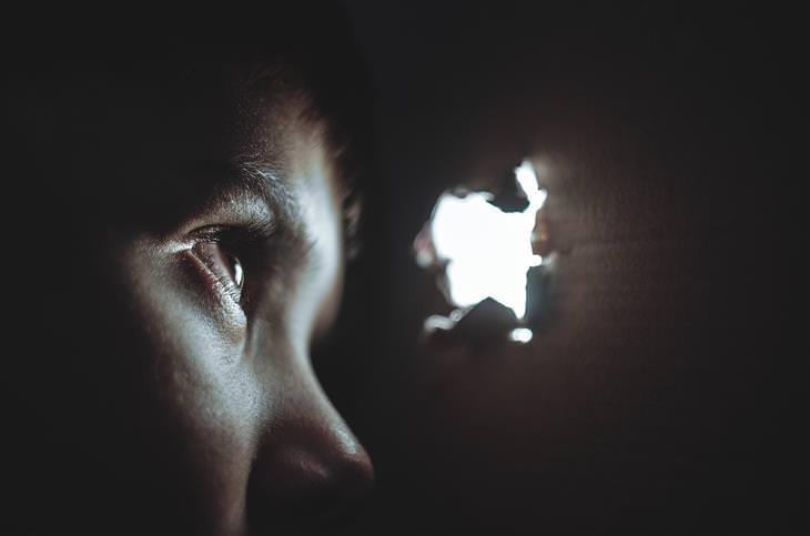 מדריך להתמודדות עם פחדים נפוצים של ילדים בכל גיל: ילד מסתתר במקום חשוך ומציץ דרך חור בקיר