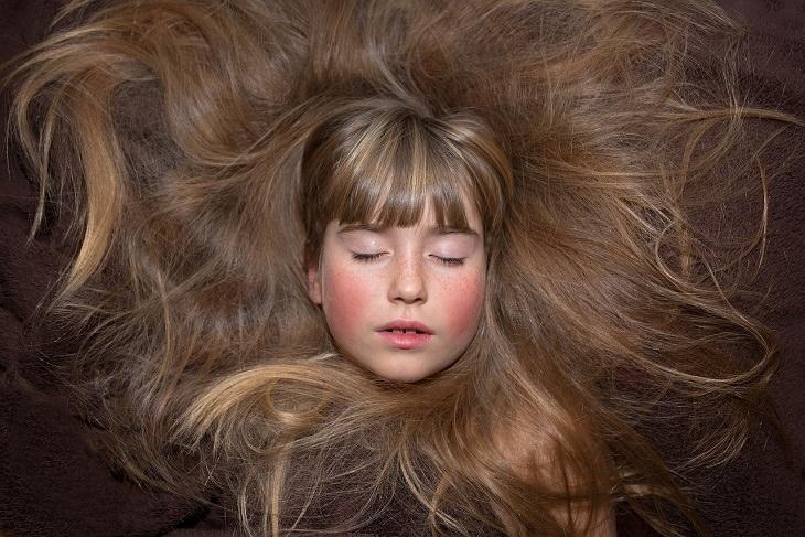 יתרונות בריאותיים של שמן נר הלילה: ילדה עם שיער ארוך המקיף את פניה
