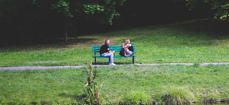 למה לגברים קשה להקשיב לנשים: גבר ואישה יושבים על ספסל בפארק ומדברים