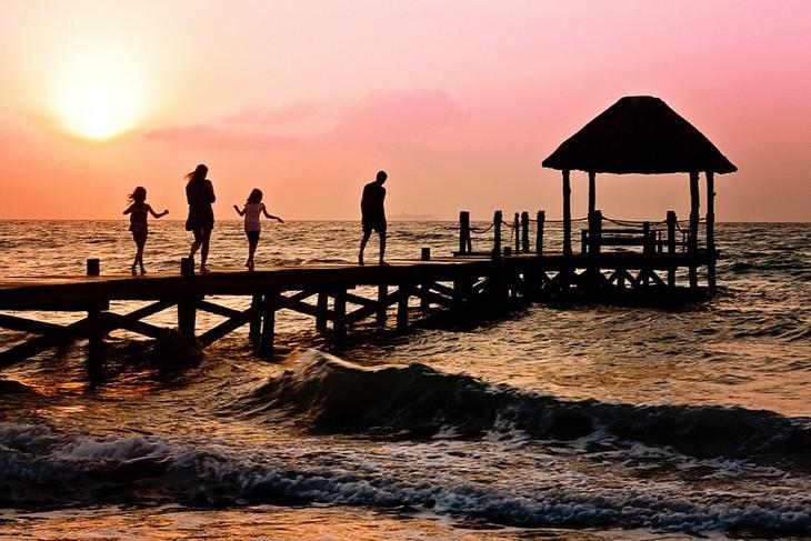 טעויות שהורים עושים בטיולים עם ילדים: משפחה הולכת על מזח במהלך שקיעה