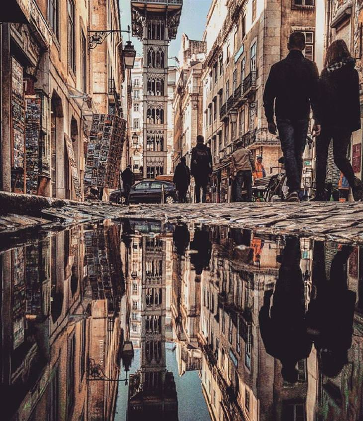 נוף עירוני משתקף בשלוליות: זוג מתהלך ברחוב בליסבון, פורטוגל