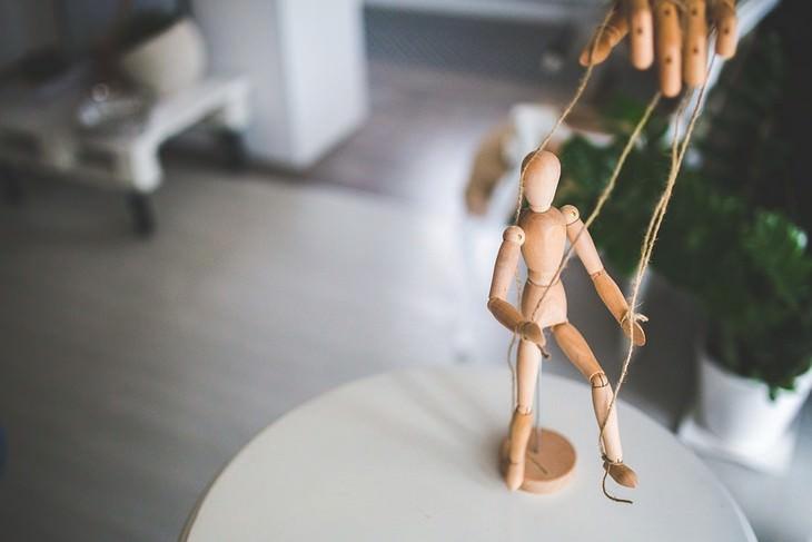 סימנים שעושים עליכם מניפולציות: יד מעץ מפעילה בובה מעץ על חוט
