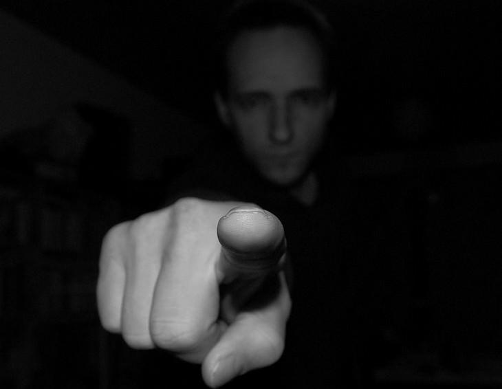 סימנים שעושים עליכם מניפולציות: גבר בחשיכה עם אצבע מורמת מולו