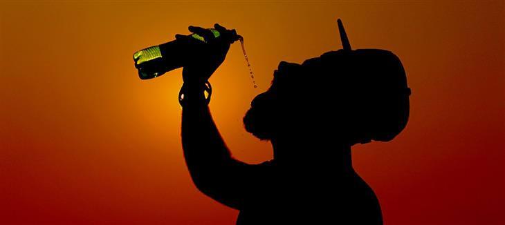מיתוסים שמאמינים בהם בגלל פרסומות: צללית של איש שותה משקה מבקבוק בשעת שקיעה
