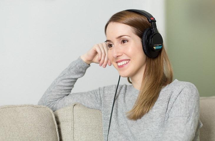"""עצות זוגיות של ד""""ר פיל: אישה מחוייכת יושבת על ספה עם אוזניות לראשה"""