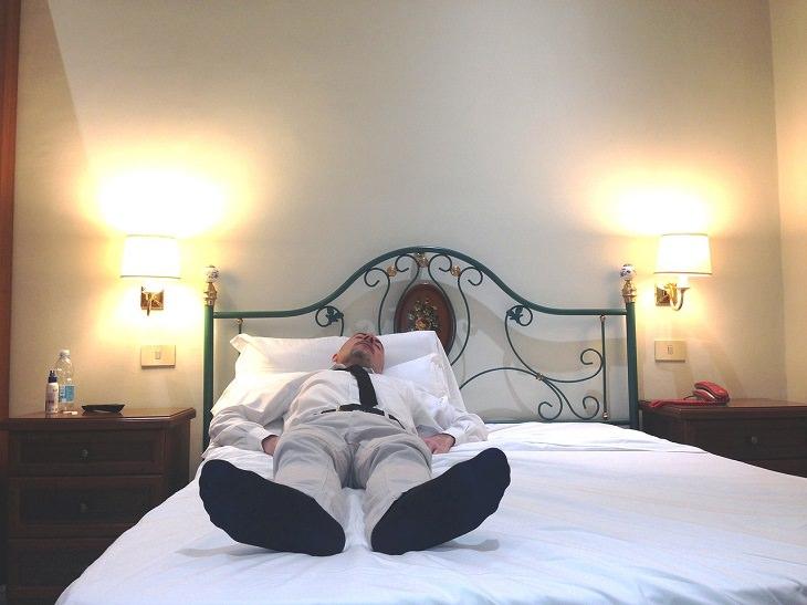 איך להתאושש משנת לילה רעה: אדם בלבוש רשמי מנמנם במיטה