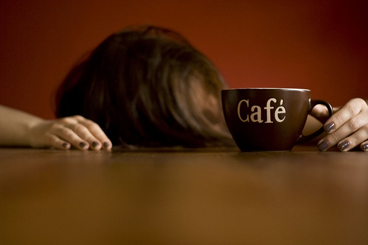 איך להתאושש משנת לילה רעה: אשה שראשה שמוט על השולחן והיא מחזיקה כוס קפה