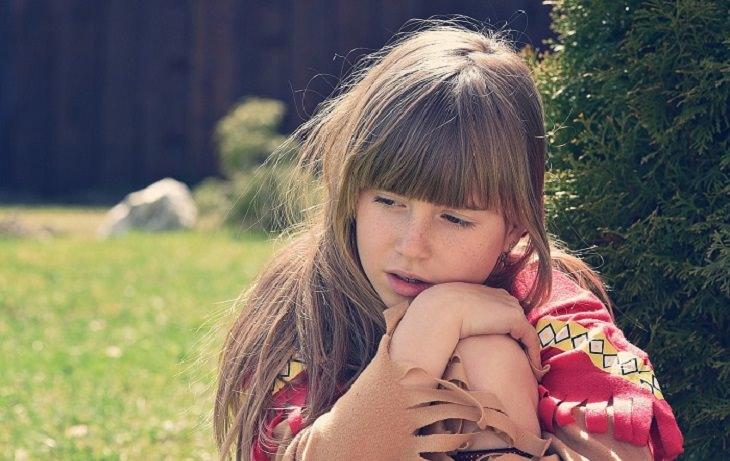 הסיבות שמאחורי בעיות התנהגות של ילדים - ילדה מהורהרת יושבת על דשא