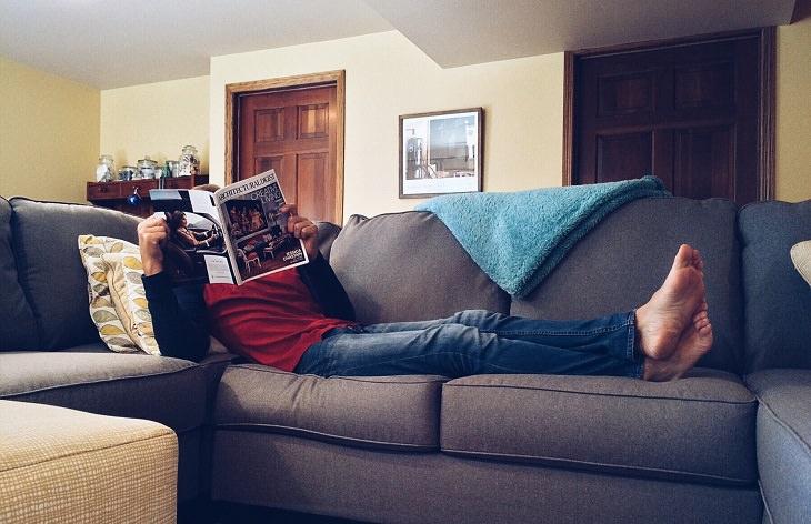 מה מפריע לגברים ונשים: גבר שוכב על ספה וקורא מגזין