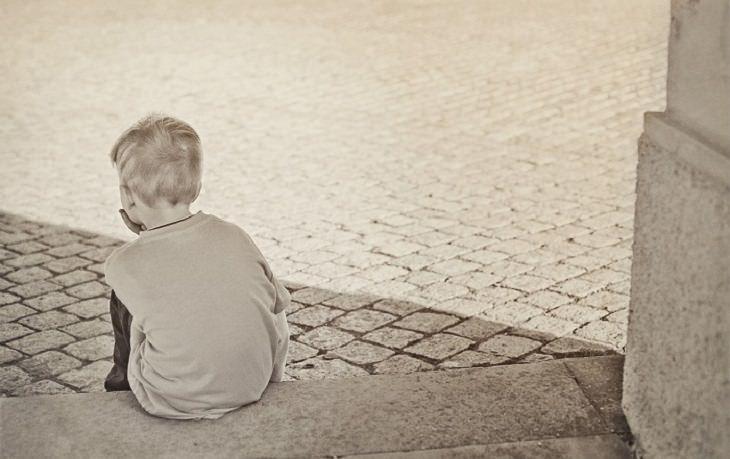 הסיבות שמאחורי בעיות התנהגות של ילדים - ילד עם הגב למצלמה יושב על המדרכה