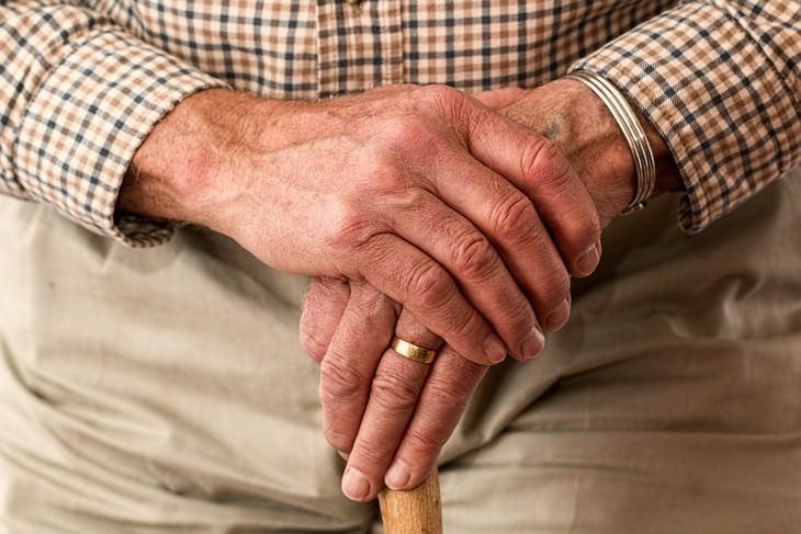 בדיחה על איש זקן שהתחתן עם צעירה: ידיים מוצלבות של אדם זקן על מקל הליכה