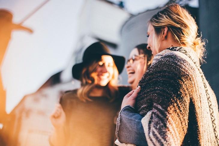איך למשוך אליכם אנשים במהרה: שלוש נשים עומדות יחדיו וצוחקות