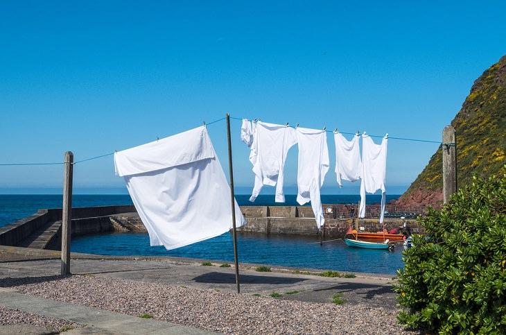 טיפים לכביסה ושמירה על בגדים: כביסה לבנה תלויה על חבל ליד הים