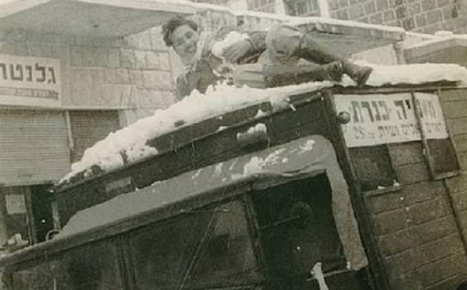 מבחן טריוויה: גבר משתעשע במשחק עם שלג, על גבי רכב תובלה