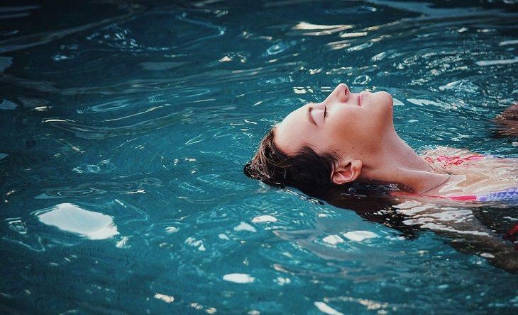 יתרונות שחייה: אישה מאושרת צפה במים