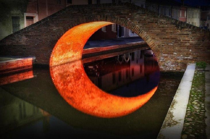תמונות של שלמות: תאורה מתחת לגשר פוגשת את המים שמתחתיה ויוצרת צורת חצי ירח