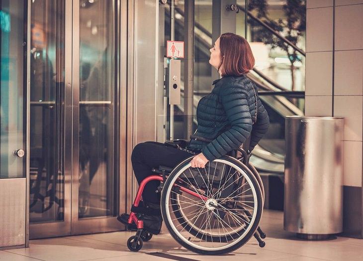 שירותים מונגשים: אישה על כיסא גלגלים מחכה למעלית