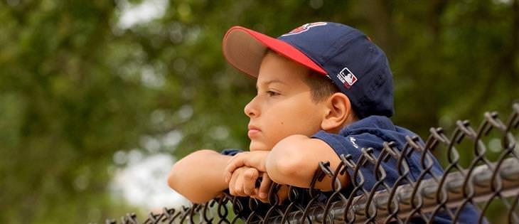 איך להתמודד עם תלונות של ילדים על בית הספר: ילד מדוכדך נשען על גדר
